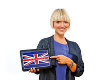 Attractive blond woman holding tablet with english language sign. On screen royalty free stock photography