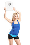 Attractive blond woman holding a weight scale Royalty Free Stock Photo