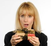 Attractive blond woman holding wrapped present with surprised expression Royalty Free Stock Photography
