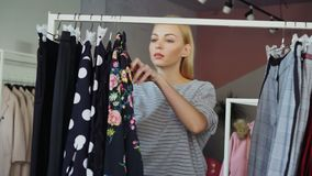 Attractive blond woman is looking at fashionable clothing on rails, moving them aside swiftly after checking them. She. Attractive blond woman is looking at stock video footage
