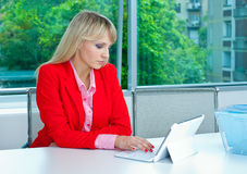 Attractive blond woman in office with laptop Royalty Free Stock Image