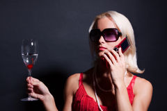 Attractive blond woman with phone and glass Stock Photos