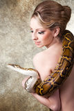 Attractive blond woman with python on grey Royalty Free Stock Photos