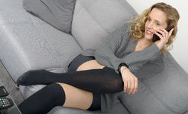 Attractive blond woman relaxing on the sofa in her home Royalty Free Stock Photos