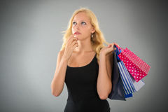 Attractive blond woman with shopping bags forgot something. Young blond woman with shopping bags is something forgotten on gray background Royalty Free Stock Images