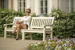 Attractive blond woman sitting on a bench in the garden. Stock Photography