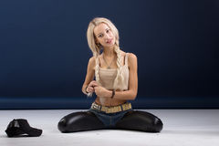 Attractive blond woman sitting on her knees Stock Image