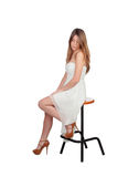 Attractive blond woman sitting on a stool Royalty Free Stock Photos