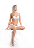 An attractive blond woman sitting in white erotic lingerie Royalty Free Stock Photo