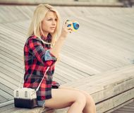 Attractive blond woman sitting on the wooden floor and photographed with a toy camera Royalty Free Stock Photos