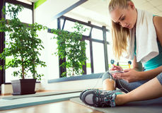 Attractive blond woman with smart phone, resting after gym workout Stock Image