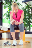 Attractive blond woman with smart phone, resting after gym workout Stock Images
