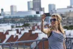 An attractive blond woman taking a selfie on a mobile phone outdoors. Royalty Free Stock Image