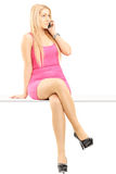 Attractive blond woman talking on a phone and sitting on a table Stock Images