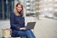 Attractive blond woman using her laptop in town. Sitting on steps in front of a commercial building in the sunshine smiling as she works stock image