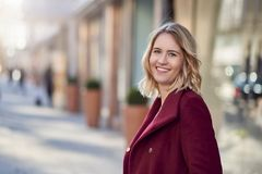 Attractive blond woman in warm maroon overcoat smiling. Attractive blond woman in warm maroon overcoat standing in a city street turning to look at the camera Stock Image
