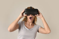 Attractive blond woman wearing headset VR virtual reality vision goggles watching video. Young attractive blond woman wearing headset VR virtual reality vision Stock Photo