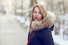 Attractive blond woman wearing a warm jacket. With fur lined hood standing outdoors in winter on a snowy road turning to look back at the camera Royalty Free Stock Image