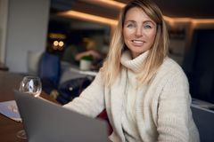 Attractive blond woman working on a laptop. Smiling at the camera while enjoying a glass of wine indoors at a pub or restaurant Royalty Free Stock Photography