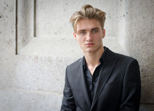 Attractive blond young man in jacket, against a wall Stock Image