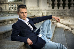 Attractive blond young man sitting on stone stair steps outside Royalty Free Stock Images