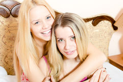 2 attractive blond young women beautiful girlfriends in pajamas having fun hugging sitting on white bed happy smiling Stock Photo