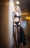 Attractive blonde in black lingerie posing provocatively indoor Royalty Free Stock Photos