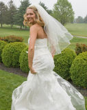 Attractive Blonde Bride running outside in gown royalty free stock image