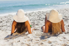 Attractive blonde and brunette in bikinis lying on the sand Stock Images