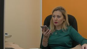 Blonde business woman using smartphone and computer and working in office. Attractive blonde businesswoman using smartphone and working on computer with mouse in stock video