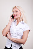 Attractive blonde calling by mobile Royalty Free Stock Image