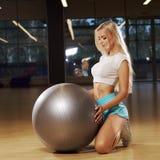 Blonde female model kneeling and holding balance ball Stock Photos