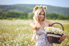Attractive blonde in chamomile field. Young woman in wreath Royalty Free Stock Image
