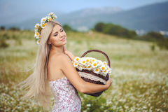 Attractive blonde in chamomile field. Young woman in wreath Stock Photo
