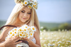Attractive blonde in chamomile field. Young woman in wreath Royalty Free Stock Photography