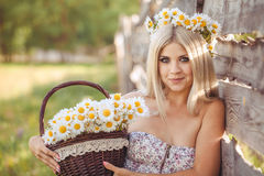 Attractive blonde in chamomile field. Young woman in wreath Stock Images