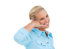 Attractive blonde doing a symbol of phone with her hand and look Stock Images