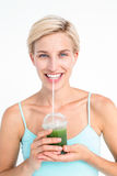 Attractive blonde drinking green juice Royalty Free Stock Images