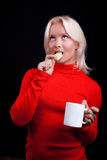 Attractive blonde drinking tea with cookies. Attractive playful blonde drinking tea with cookies Royalty Free Stock Images