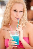 Attractive blonde drinks a blue cocktail Royalty Free Stock Image