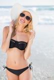 Attractive blonde in elegant black bikini smiling at camera Royalty Free Stock Photos