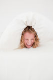 Attractive blonde female balled-up in a duvet Royalty Free Stock Images