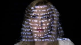 Attractive blonde female computer worker scrubbing through binary codes while digital data is projected on her face -. Attractive blonde female computer worker stock footage
