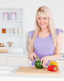 Attractive blonde female cutting vegetables Stock Photography