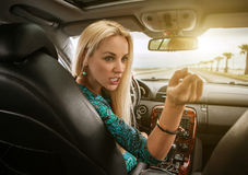 Attractive blonde female emotional talks to rear seat passenger Stock Photography