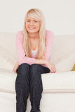 Attractive blonde female posing on a sofa Royalty Free Stock Photo