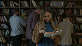 Gorgeous female student reading a book in library stock video footage