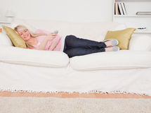 Attractive blonde female watching tv on a sofa Stock Images