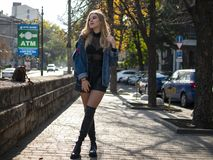 Attractive blonde with flowing hair in leather boots standing on the street in full growth