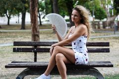 Attractive Blonde Girl With Curly Hair Sitting on the Bench in a. Park and Cooling Herself Down With a Paper Fan Stock Photography